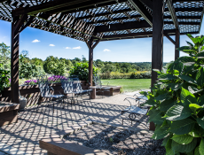 A sitting area surrounded by greenery and flowers, outside of the Mountainview Manor